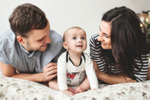 JFS Adoption - Home Studies. A young couple plays with their adopted baby.