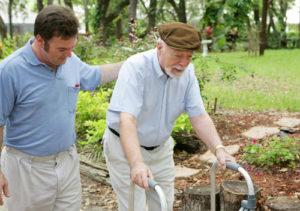 JFS Care. An elderly man using a walker, helped by a caregiver.
