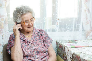 JFS Care - Senior Engagement. An elderly woman talking on the phone with a friendly volunteer.
