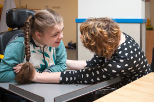 Contact JFS Richmond. A disabled girl is helped by a caregiver.