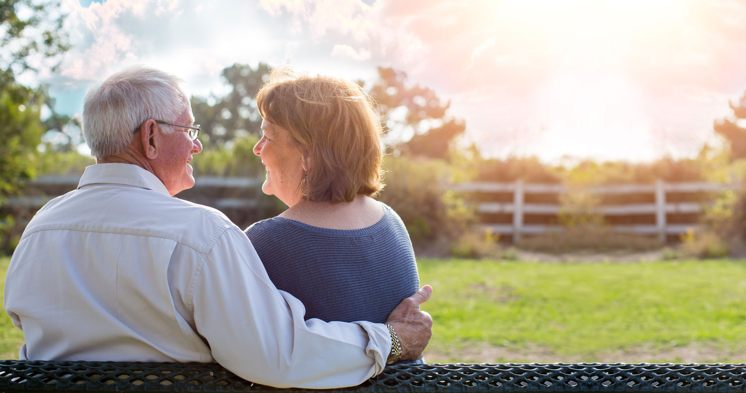 A Senior couple sits on a park bench watching the sunset